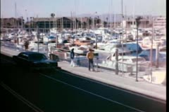 Car driving by boats moored in  harbor Stock Footage