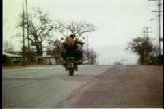 Rear view of man and woman riding motorcycle on country road Stock Footage