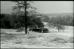 Man in 1940s car driving up to farmhouse Stock Footage