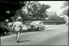 Rear view of man running towards getaway car Stock Footage