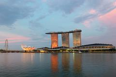 Singapore flyer and famous hotel of marina bay sands on sunset Stock Photos
