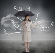 Businesswoman with jumbled arrows holding umbrella - stock photo