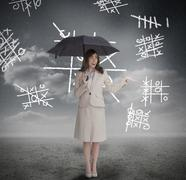 Businesswoman with noughts and crosses holding umbrella - stock photo
