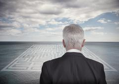 Businessman looking at landscape and maze Stock Photos
