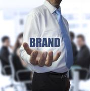 Smart businessman holding the word brand - stock photo