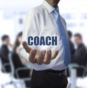 Elegant businessman holding the word coach - stock photo