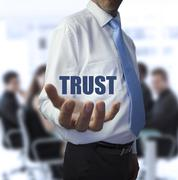 Smart businessman holding the word trust - stock photo
