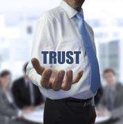 Elegant businessman holding the word trust - stock photo