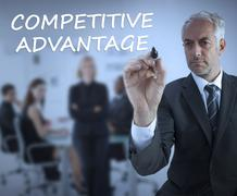 Sophisticated businessman writing competitive advantage Stock Photos
