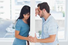 Divided couple are separated by white wall - stock photo