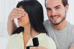 Smiling man about to propose hiding eyes of his girlfriend Stock Photos