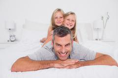 Stock Photo of Portrait of a man giving a piggy back to his children
