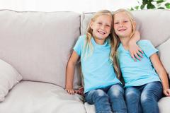 Stock Photo of Blonde twins sitting on a couch