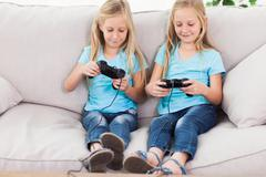 Stock Photo of Cute twins playing video games together