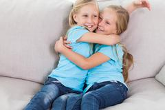 Stock Photo of Young twins embracing each other sitting on a couch