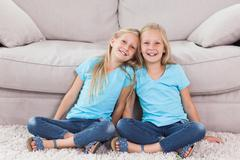 Stock Photo of Twins sitting on a carpet