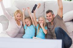 Cute twins and parents raising arms while watching television - stock photo