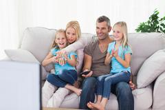 Cute twins and parents watching television - stock photo