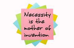 "Proverb "" necessity is the mother of invention "" written on bunch of sticky n Stock Photos"