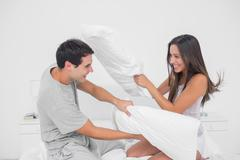 Couple fighting together with pillows - stock photo