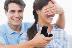 Man hiding his girlfriend eyes and offering her an engagement ring - stock photo