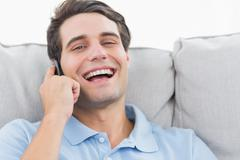 Stock Photo of Man laughing while having a phone conversation