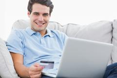 Portrait of a man using his credit card to purchase online - stock photo