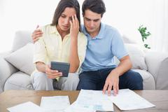 Fearful couple doing their accounts - stock photo