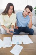 Concerned couple doing their accounts - stock photo