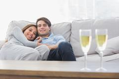 Beautiful couple resting on a couch with flutes of champagne - stock photo