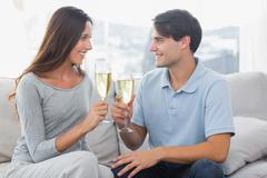 Lovers clinking their flutes of champagne Stock Photos
