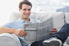 Man reading a newspaper sat on a couch Stock Photos