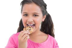 Cute little girl eating a cookie - stock photo