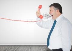 Mature businessman screaming on the phone - stock photo