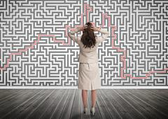 Puzzled businesswoman looking at a maze Stock Photos