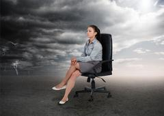 Stock Photo of Businesswoman sitting in middle of opposite weather settings