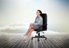 Businesswoman sitting on a chair Stock Photos