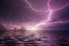 lightning over water - stock photo