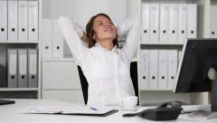 Businesswoman relaxing in office - stock footage