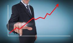 Stock Photo of Businessman selecting a red arrow pointing up on a chart