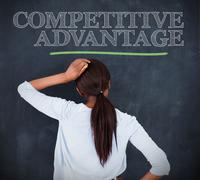 Woman looking at the word competitive advantage - stock photo