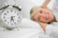 Alarm clock annoying blonde woman in bed - stock photo