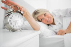 Stock Photo of Blonde woman turning off alarm clock