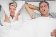 Man snoring loudly as partner blocks her ears - stock photo