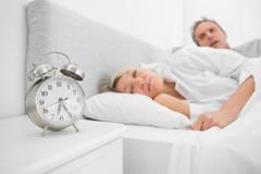 Man looking at ringing alarm clock Stock Photos