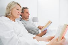 Relaxed couple reading books in bed - stock photo