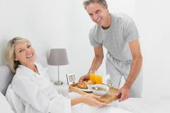 Stock Photo of Considerate man giving breakfast in bed to his partner