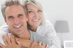 Stock Photo of Affectionate couple smiling at camera