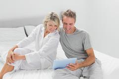 Happy couple using their digital tablet - stock photo