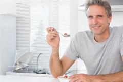 Stock Photo of Happy man having cereal for breakfast in kitchen